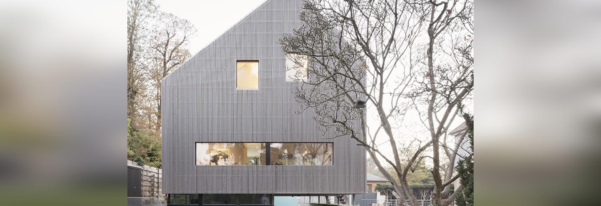 karawitz wickelt asymetrisches Haus völlig im grauen Lärchenholz in Frankreich ein