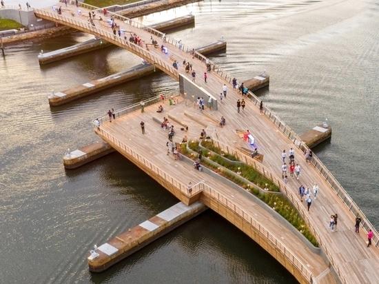 Gebogene Fußgängerbrücke verbindet zwei Parks am Flussufer in Providence