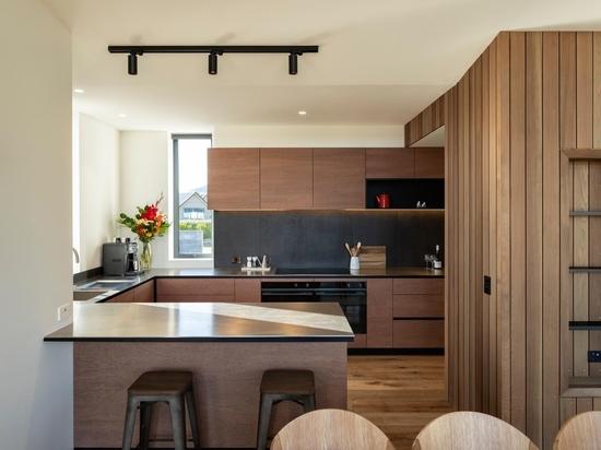Dunkle vertikale Holzverkleidungen an der Außenseite dieses modernen Hauses verleihen ihm eine starke Persönlichkeit