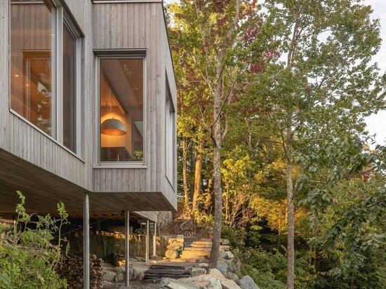 Ein Haus im Wald, verkleidet im östlichen Zederngleis, erhebt sich über die umgebende felsige Landschaft